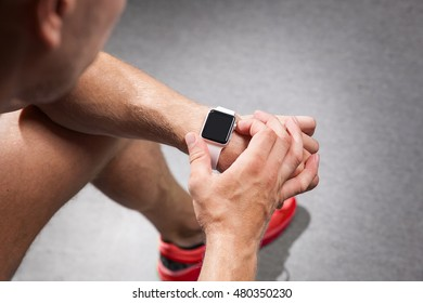 young man using fitness smart watch before exercise.