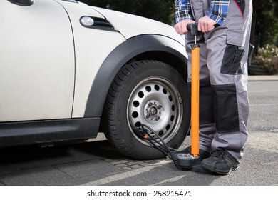 A young man is using foot-operated air pump to refill a car wheel.