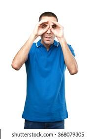 Young man using his hands as binoculars