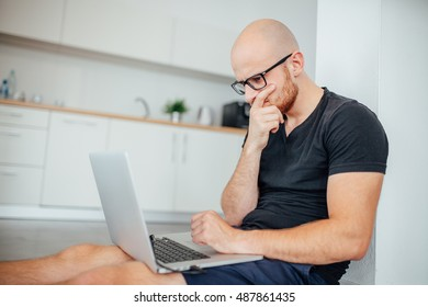 Young man is using his laptop pc. Kitchen background.