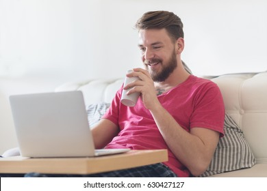 Young man using  his laptop in a bedroom.