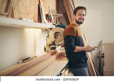 Young man using his phone and looking up with a smile while standing casually in his carpentry workshop