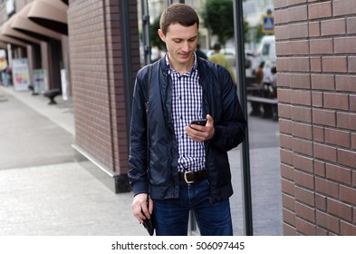Young man using his phone on the street