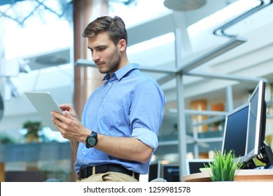Young man using his tablet in the office.