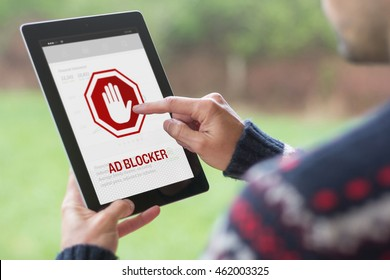 A young man is using his tablet in a green nature background, with ad blocker on the screen