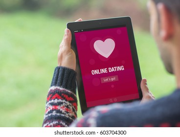 A young man is using his tablet outdoor and using online dating app