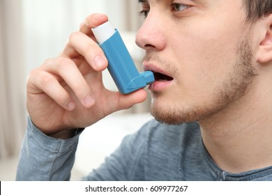 Young man using inhaler during asthmatic attack at home, closeup