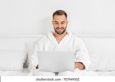 Young man using laptop in hotel room