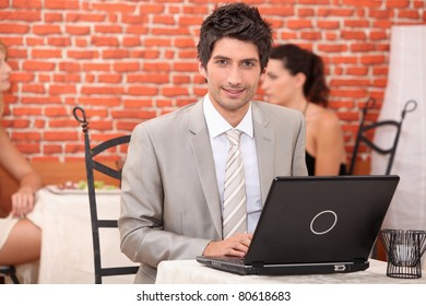 Young man using laptop in a restaurant