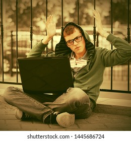 Young man using laptop sitting on sidewalk  Stylish trendy teenage male model in green hoodie and gray jeans