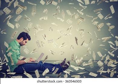 Young man using a laptop sitting on a floor building online business making money dollar bills cash falling down. Money rain. Beginner IT entrepreneur success economy concept