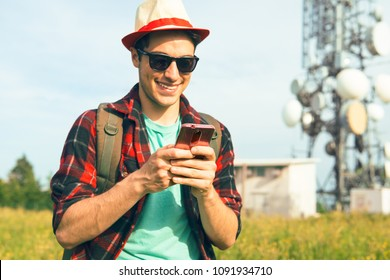 Young man using mobile outdoors over communication antenna background - Teenager male texting phone message on green field with telecommunication tower - Concept of electrosmog and modern technology