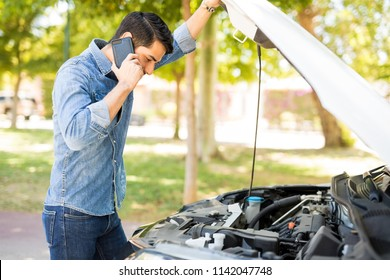 Young man using mobile phone while looking at broken down car on street