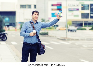 Young man using mobile phone app waiting for rideshare – Millennial business man with hand up calling taxi hailing from sidewalk – Male passenger after work in city centre using online map to call cab