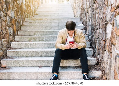 Young man using mobile phone while sitting outdoors
