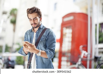 Young man using mobile phone in street