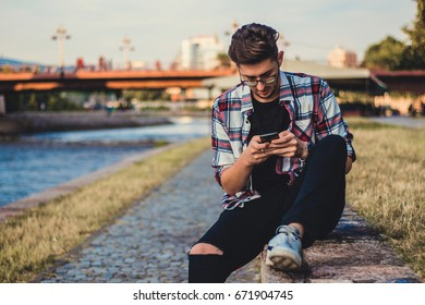 Young man using mobile phone outside.