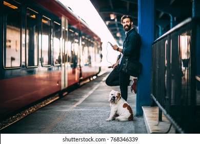 Young man using mobile phone at train station