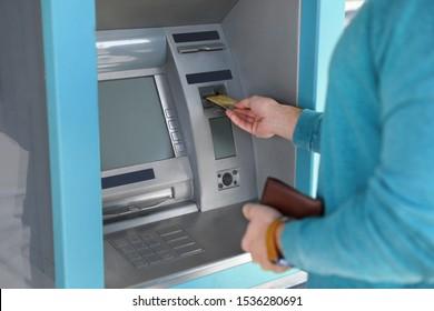 Young man using modern cash machine outdoors, closeup