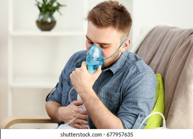 Young man using nebulizer for asthma and respiratory diseases at home