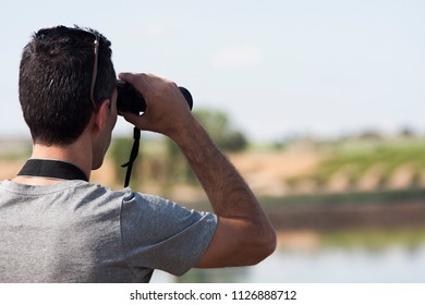 a young man using a pair of binoculars in the nature