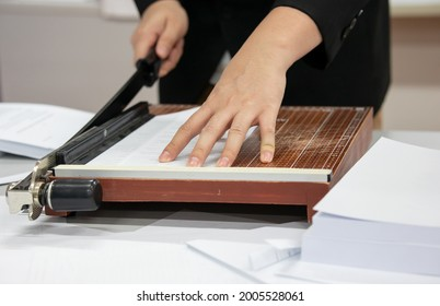 A young man using a Paper cutter to make a book in the office. cutting paper on desk.  office equipment