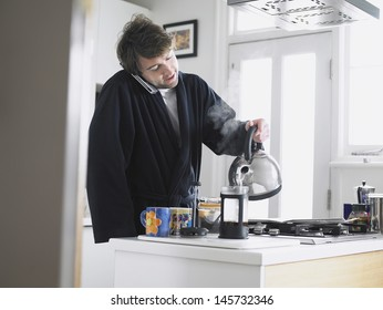 Young man using phone while pouring water into coffee plunger in kitchen