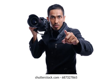 Young man using a professional camera and pointing with finger toward