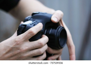 Young man using a professional camera takes pictures.