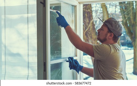 young man is using a rag and squeegee while cleaning windows. professional window cleaner.