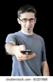 A young man using a remote control on black background.