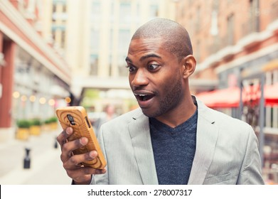 Young man using smart phone. Businessman holding mobile smartphone using app texting sms message wearing jacket