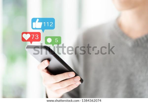 ソーシャルネットワークでスマートフォンを使う若者
