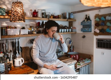 young man using smartphone and drinking coffee in his kitchen