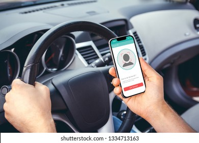 young man using smartphone with face id technology in a car