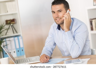 young man using smartphone in front of laptop