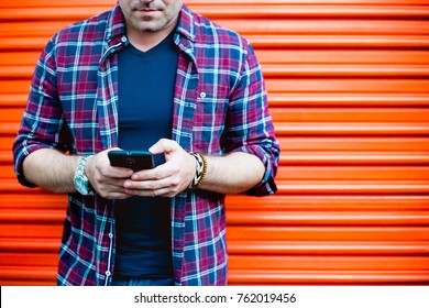 Young man using a smartphone in front of an orange storage door.  Dressed casually. Urban life style, technology, shopping, roadside assistance, moving, self storage and job hunting concept.