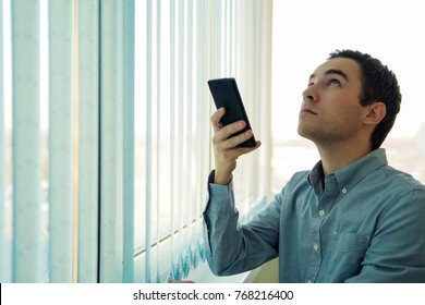 Young man using a smartphone in front of a window. Control vertical blinds with your phone. To open a window with a mobile app. Smart home. modern technology in the office.