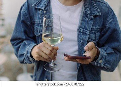 Young man using smartphone and holding glass of white wine outdoors.