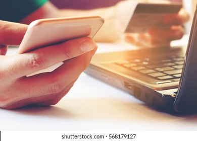 Young man using smartphone and holding credit card with laptop for searching data