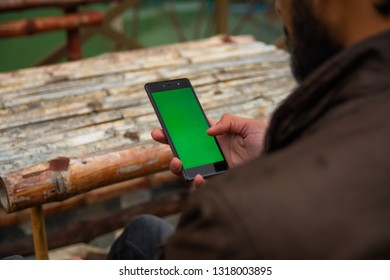 young man using smartphone mobile outdoors chroma key green screen