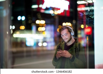 Young man using smartphone on urban street at night