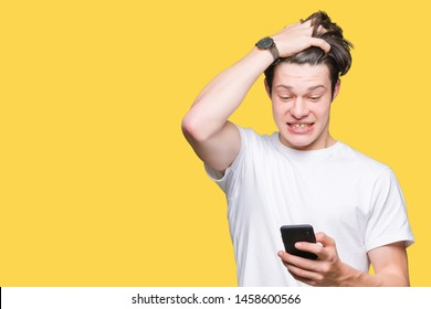 Young man using smartphone over isolated background stressed with hand on head, shocked with shame and surprise face, angry and frustrated. Fear and upset for mistake.