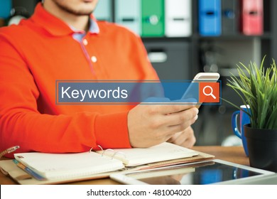 Young man using smartphone and searching KEYWORDS word on internet