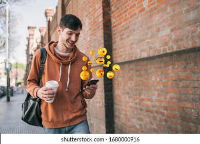 Young man using smartphone sending emojis. Outdoors. Social media concept.