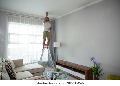 Young man using a stairs to install lights in living room at home