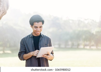Young man using tablet device in a park