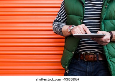 Young man using a tablet in front of an orange garage door, Dressed casually. Jeans, Vest. Urban life style, technology, online, business, shopping, fashion and job hunting concept.