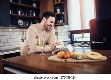 Young man using tablet in kitchen at home and drinking wine.