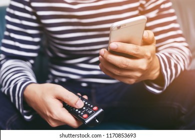 young man using television remote control and mobile smart phone  is sitting on a sofa. on or off tv.
